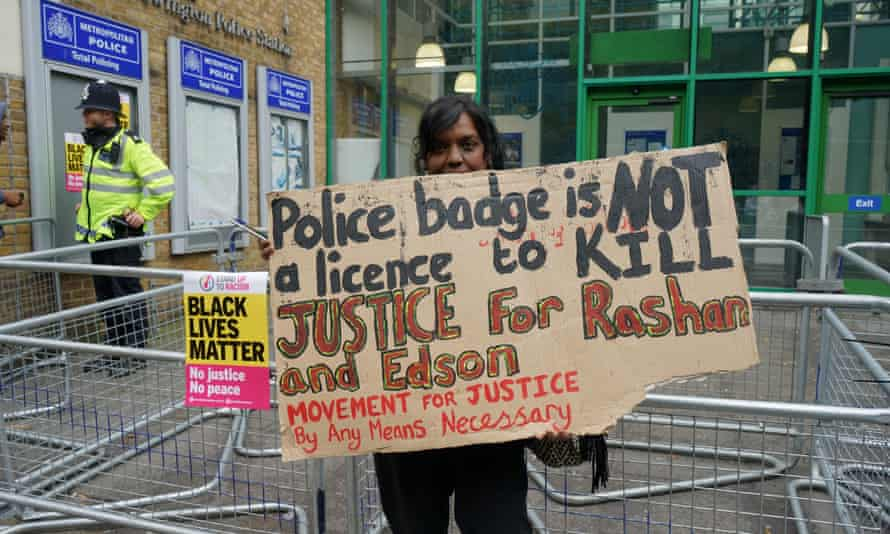 A member of the Movement for Justice group outside Stoke Newington police station in July 2017 to protest over the deaths of Edson Da Costa and 20-year-old Rashan Charles.