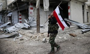 A Syrian soldier holds up the national flag as he patrols the east Aleppo neighbourhood of Tariq al-Bab.