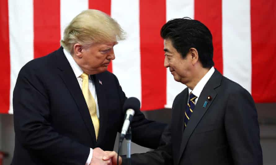 Donald Trump shakes hands with Japan's prime minister Shinzō Abe.
