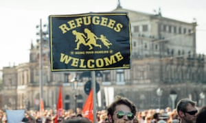 People hold up a 'Refugees Welcome' banner in Germany, where football fans have inspired their English counterparts to show their support for those fleeing warzones for Europe.