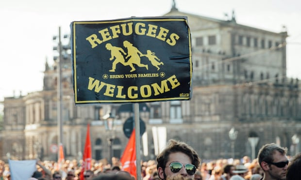 A demonstrator in Dresden, Germany holds a sign that reads 'refugees welcome' on Saturday. Photograph: Oliver Killig/dpa/Corbis