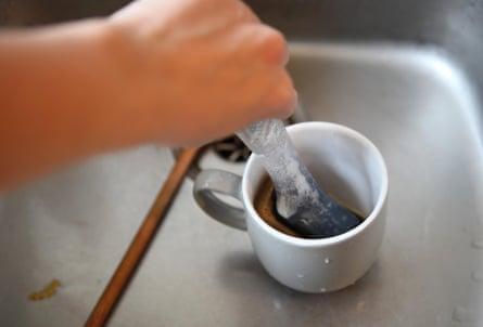 A hand washing a mug with a soap-dispensing dish brush