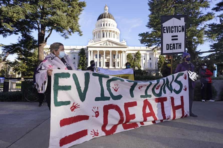 """Demonstrators gather in front of the capitol building in Sacramento, California, holding a sign saying """"Evictions = Death""""."""