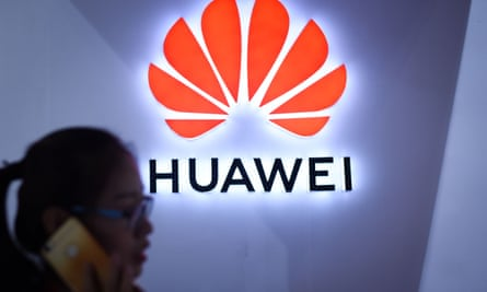 A woman uses her mobile phone in front of a Huawei logo