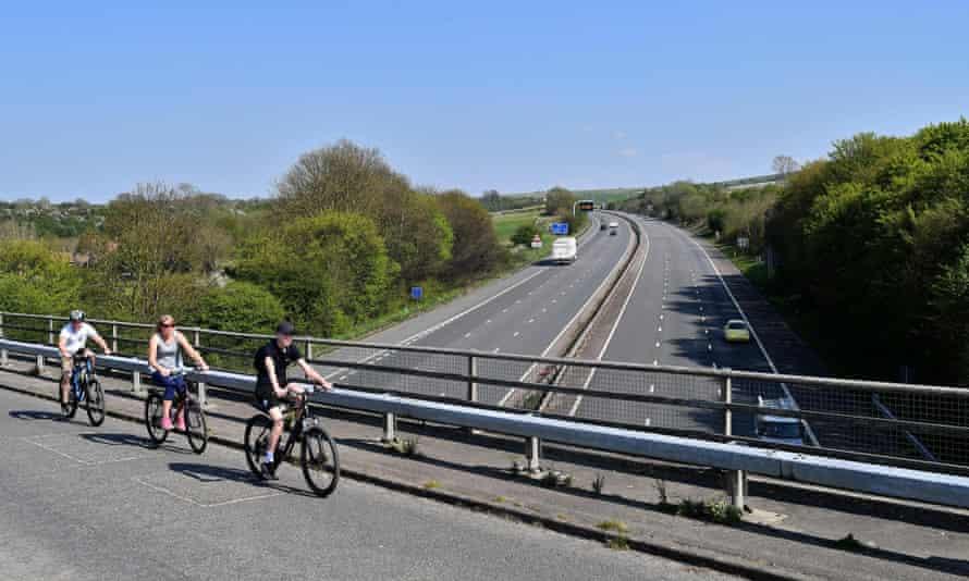 Cyclists cross a bridge over a quiet M4 motorway near Swindon in April