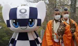 Tokyo 2020 Olympic Games mascot Miraitowa and Buddhist monks wearing protective face masks attend a ceremony to unveil a display of Olympic Symbol on Mt. Takao in Hachioji, west of Tokyo, Wednesday, 14 April 2021, to mark 100 days before the start of the Olympic Games.