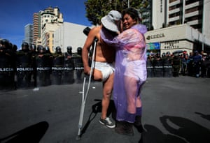 Demonstrators stand in front a riot police barricade during a protest in La Paz