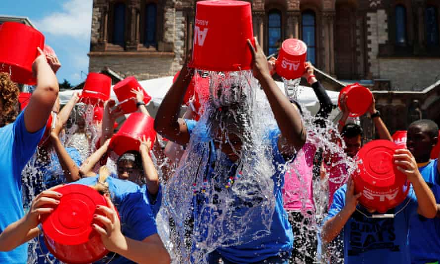 """Eleven-year-old Jahziyah Jones, with a crowd of others, pours a bucket of ice water over her head during an event to commemorate the five year anniversary of the """"ALS Ice Bucket Challenge"""