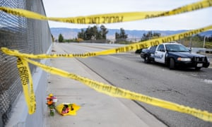 Flowers are left by the side of the blocked road leading to the Inland Regional Center.