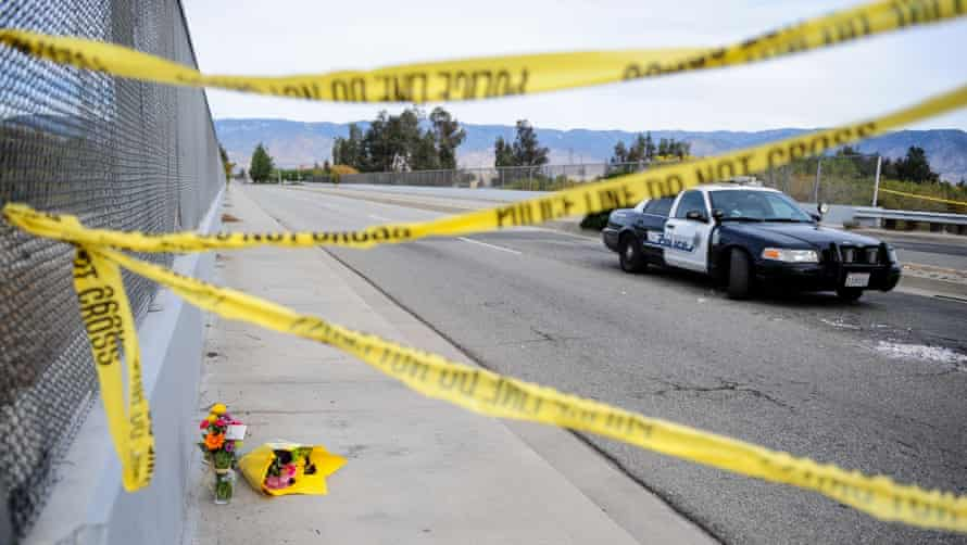 Flowers are left by the side of the road as police block the road leading to the site of the mass shooting in San Bernardino, California.