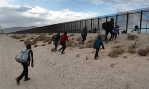 Immigrants approach the US-Mexico border fence in El Paso, Texas.