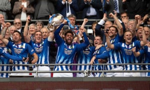 Chertsey Town's players lift the FA Vase atop the Wembley steps.