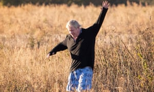 Boris Johnson running through a field of dried grass near his Oxfordshire home.
