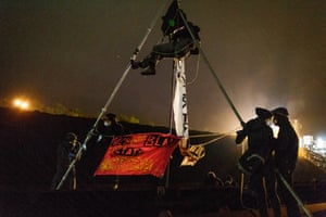 One of the activists sits atop a tripod near the conveyor belt of the plant during the blockade