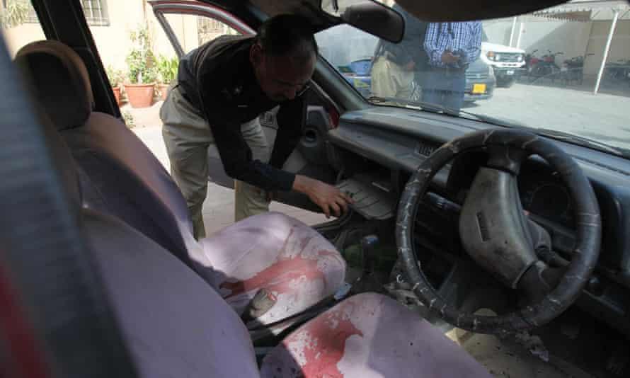 A Pakistani police officer examines a car of US citizen Debra Lobo, targeted by gunmen in Karachi on Thursday.