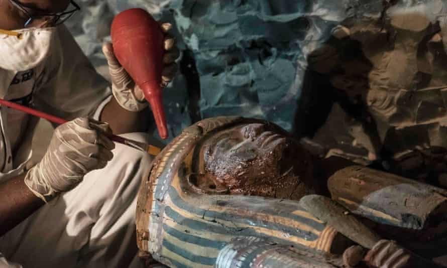 An Egyptian archaeologist restoring a wooden sarcophagus.