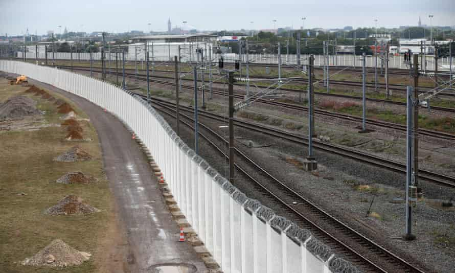 A white security fence, paid for by Britain, is intended to counter attempts by migrants to board cross-channel trains.