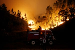 Firefighters work to put out a forest fire near Bouca