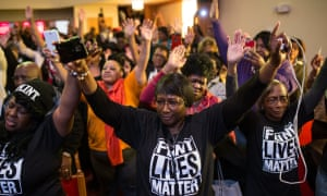 Flint residents raise their arms during a town hall