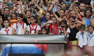People react as the caravan carrying the ashes of Fidel Castro passes them in Las Tunas, Cuba, on Friday.