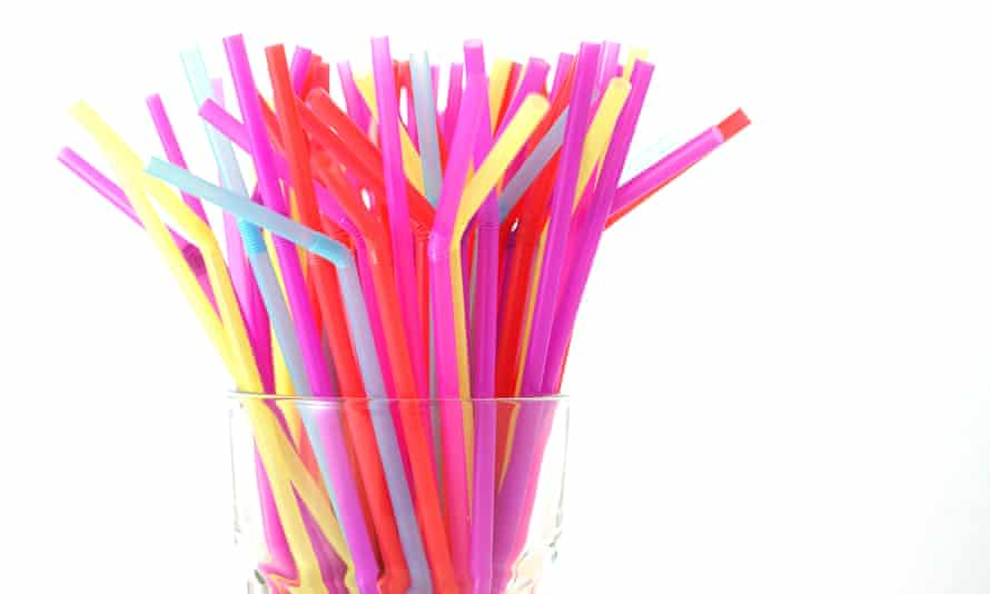 A glass filled with plastic straws.