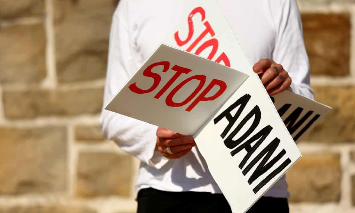 A person holds a placard at a Stop Adani protest in Sydney