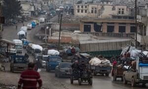 A convoy of vehicles taking Syrians to safety passes the village of Al-Mastuma, Idlib province,