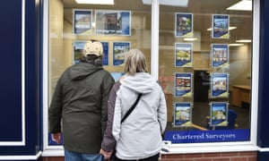 Home-seekers in Leek, Staffordshire view an estate agent window