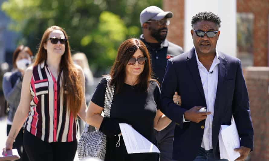 Former NFL players Ken Jenkins, right, and Clarence Vaughn III, center right, along with their wives, Amy Lewis, center, and Brooke Vaughn, left, carry tens of thousands of petitions demanding equal treatment for retired athletes