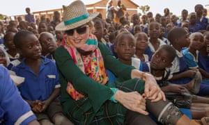 Madonna sits among Malawian children