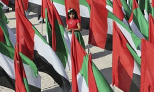 An Emirati girl in the middle of UAE flags.
