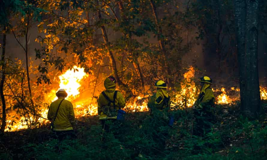 Firefighters at a house during the CZU Lightning Complex fire on Sunday in Boulder Creek, California.
