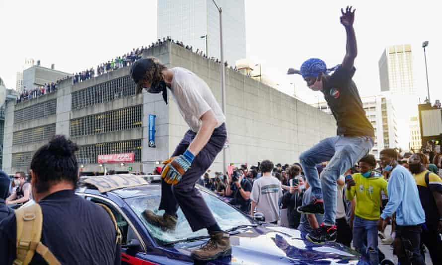 Protesters smash a police car during a protest outside CNN Center in Atlanta, Georgia.