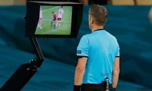 Referee Daniele Orsato checks the VAR screen before awarding Spain a penalty.