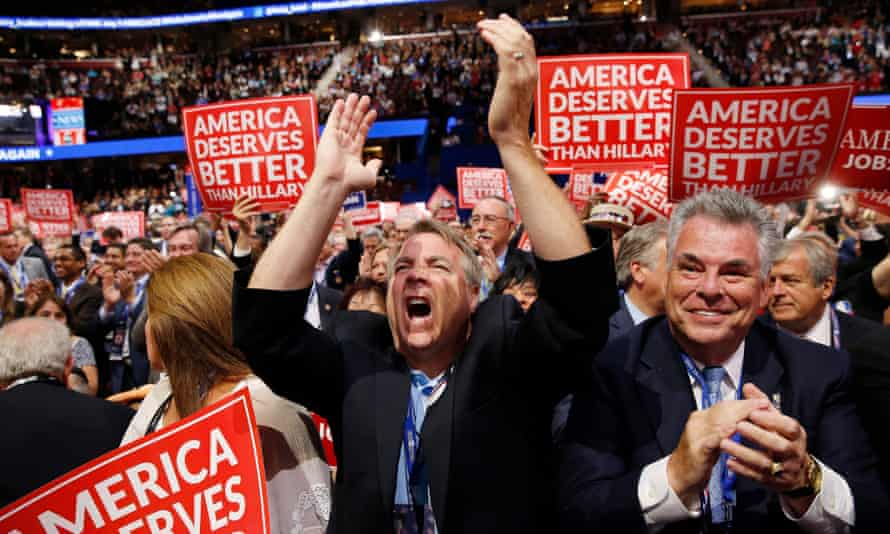 The US representative Peter King of New York and other delegates react as they watch Wisconsin Governor Scott Walker speak during the 2016 Republican National Convention.