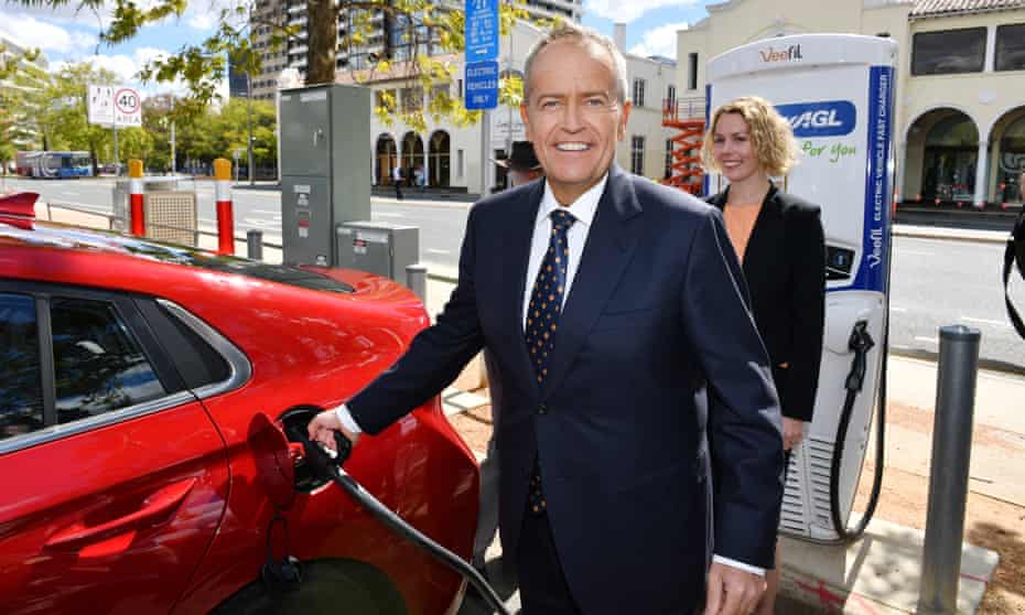 Bill Shorten charges an electric car after launching Labor's climate change action plan. A car manufacturer has called for an end to Coalition 'fear-mongering' over electric vehicles.