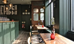 Sunlight comes through the windows in an interior image of tables and the bar at the Kings Arms, Bethnal Green, London