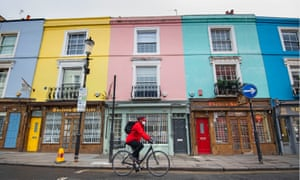 A cyclist passes closed shops on Portobello Road, west London, during the coronavirus lockdown.