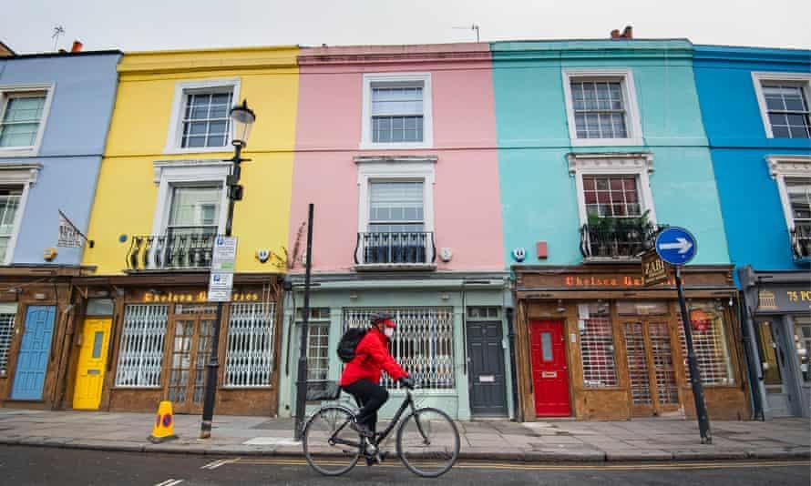 A cyclist passes closed shops on Portobello Road, west London, during the coronavirus lockdown.