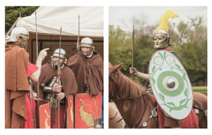 Three Roman soldiers have a conversation in their camp, and another one carrying spear-wielding soldier