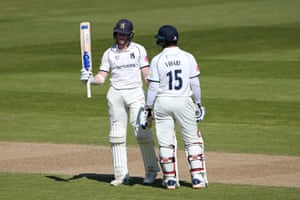 Rob Yates raises his bat to celebrate reaching his fifty