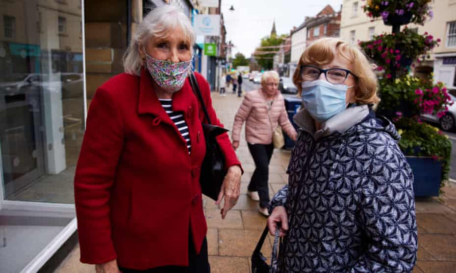 Two women wearing face masks and coats stand together in a high street