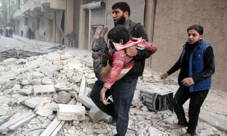 A man pulls a child from the wreckage after a Russian airstrike in Aleppo, Syria.