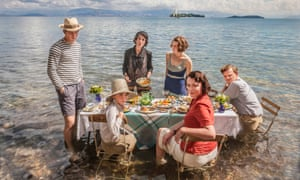 Group cast shot of The Durrells, sitting at a picnic table in shallow water on a beach