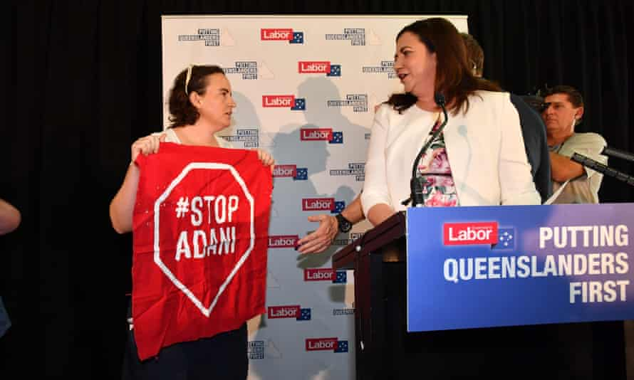 Anti-Adani coal mine protestors invade the stage as Queensland Premier Annastacia Palaszczuk (right) announces the date of the Queensland election