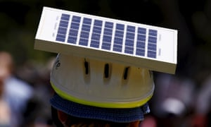 A cyclist wears a helmet with a solar panel attached as he participates in a march along the main street of Adelaide.