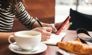 Young woman using smart phone and writing on notebook in a cafe.