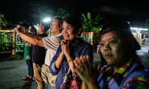 Onlookers watch as ambulances bring boys rescued from the cave to a hospital in Chiang Rai.
