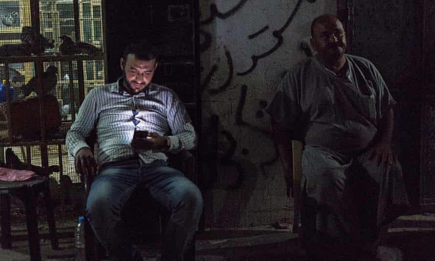 Ayman Nasser and Ashraf Kasqin sit outside a shop in the al-Shati refugee camp in Gaza City