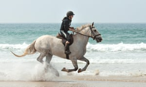 A grey horse and rider running through the surf on the beach at Gwithian, Cornwal